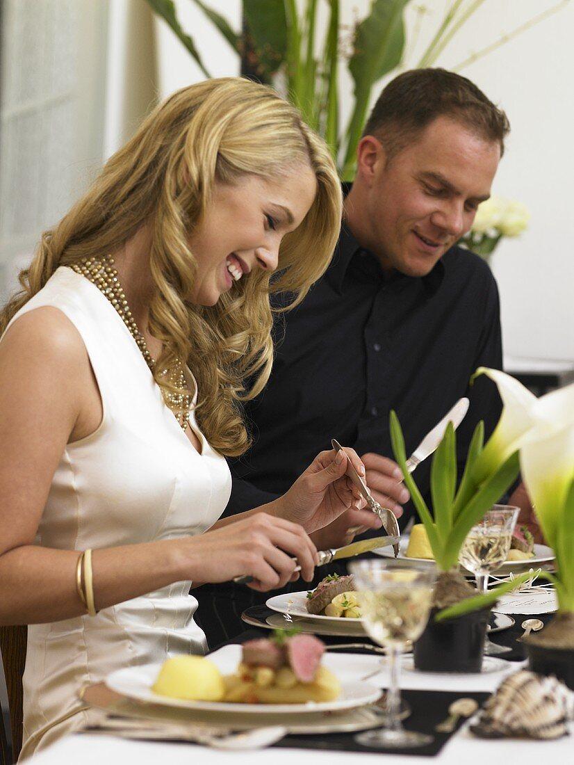 Couple eating veal fillet at elegant table