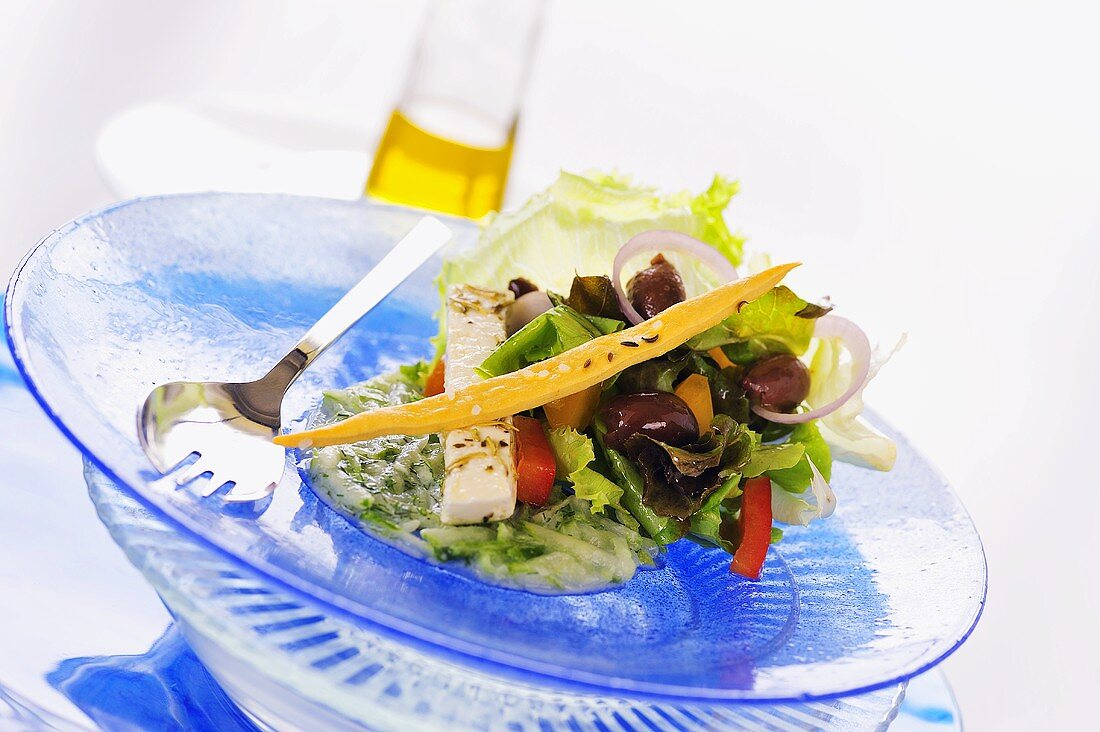 Salad leaves with marinated feta and olives