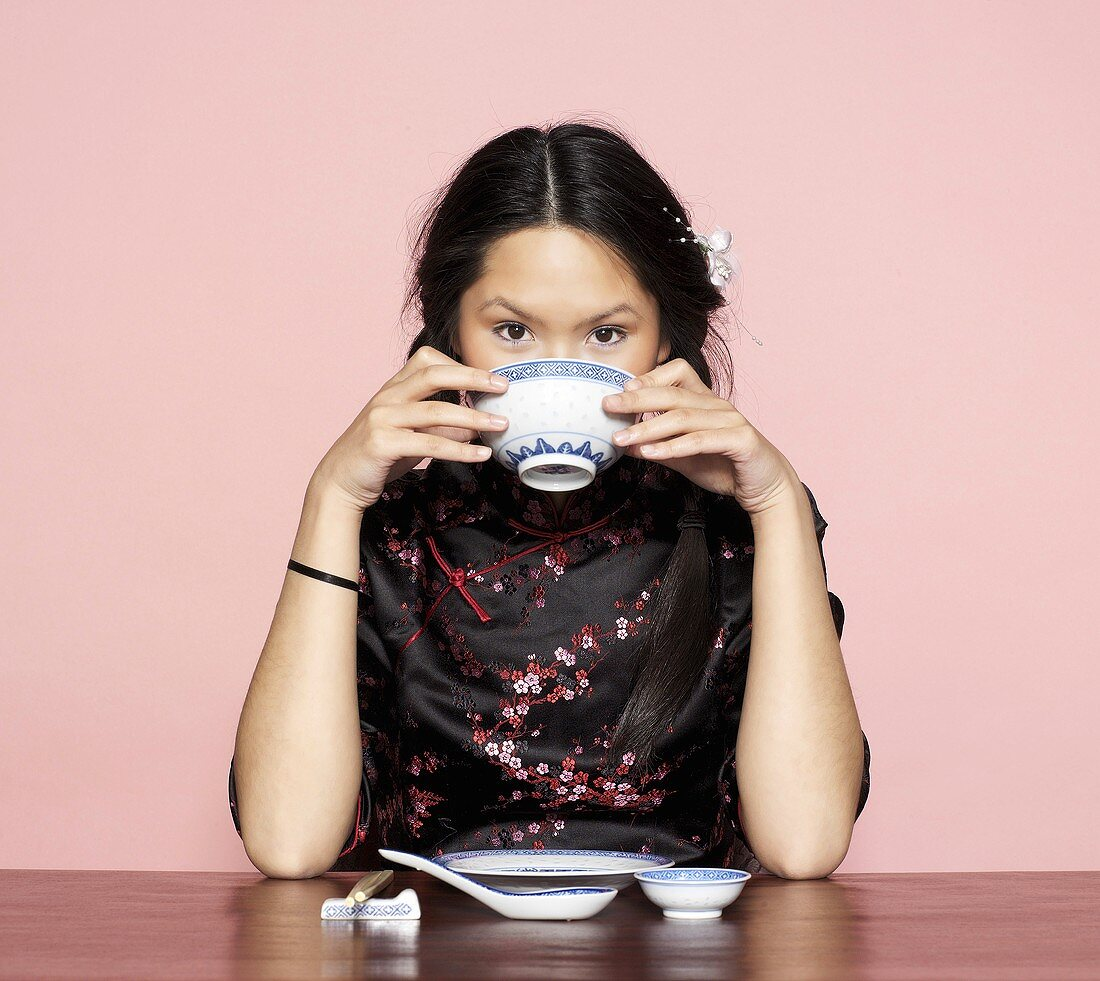 Asian woman, eating from bowl