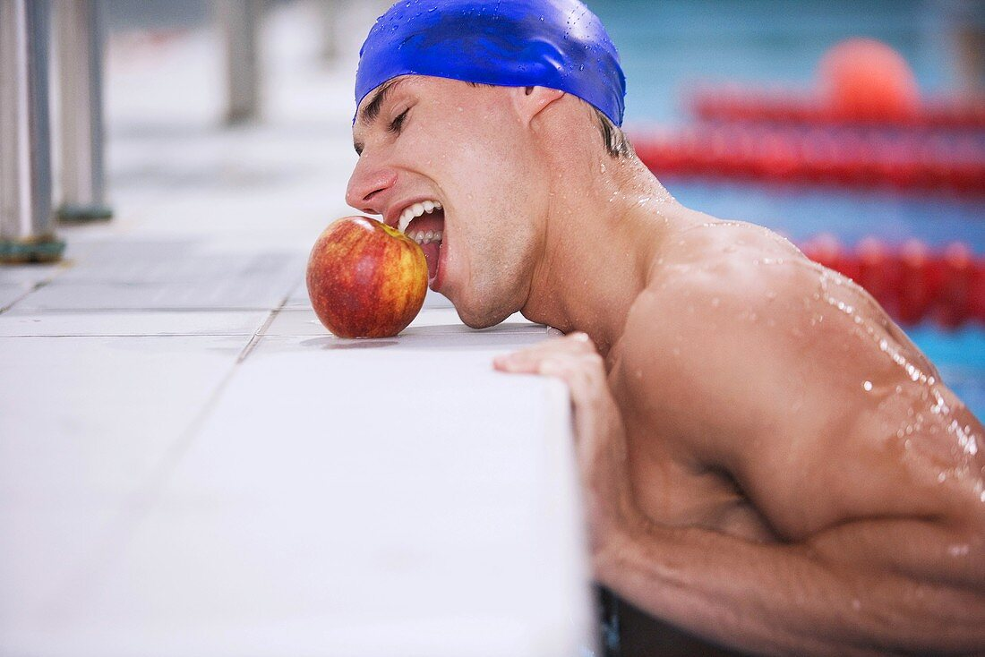 Swimmer grapping apple with mouth