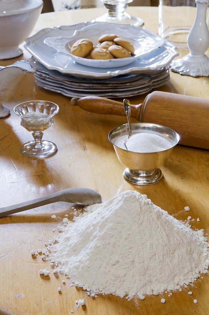 Flour, sugar, rolling pin and crockery on a table