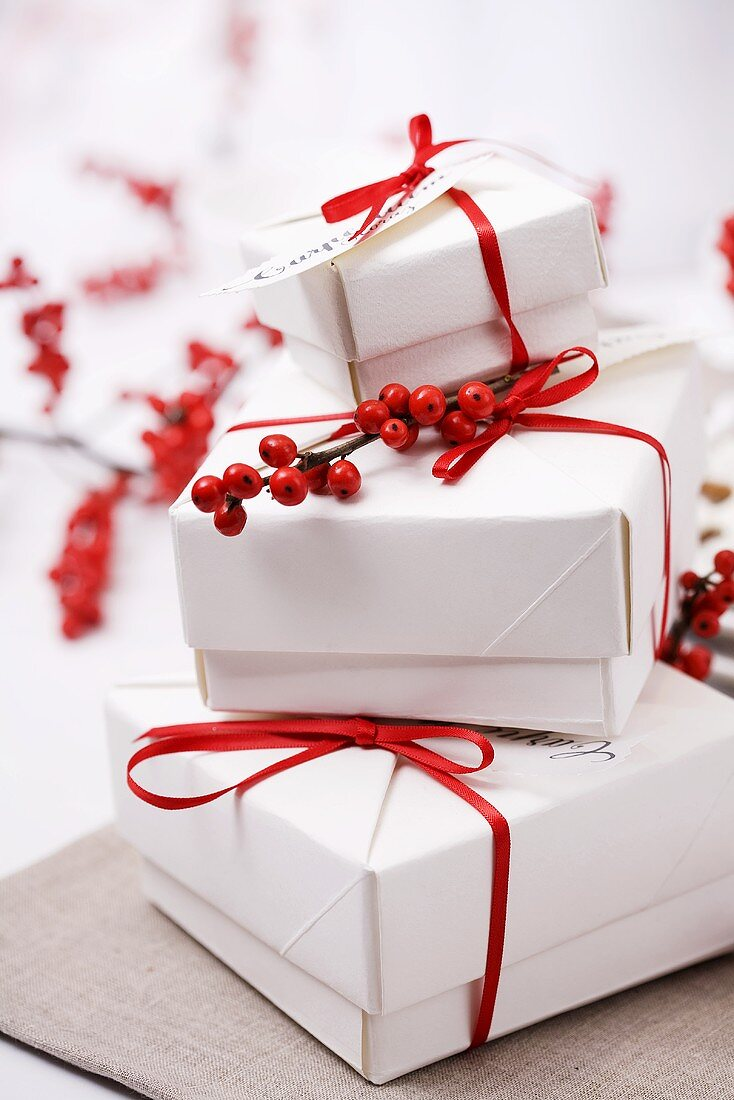 Several parcels with red gift ribbons and holly berries