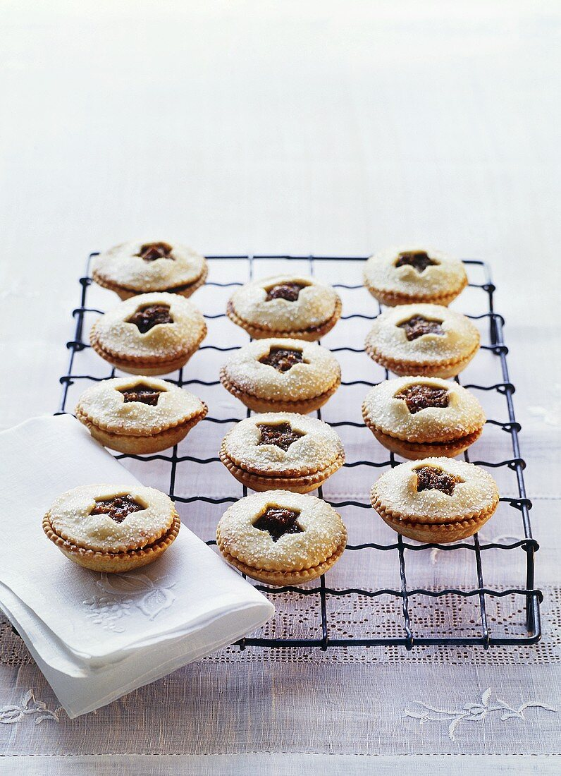 Mince pies with icing sugar on cake rack