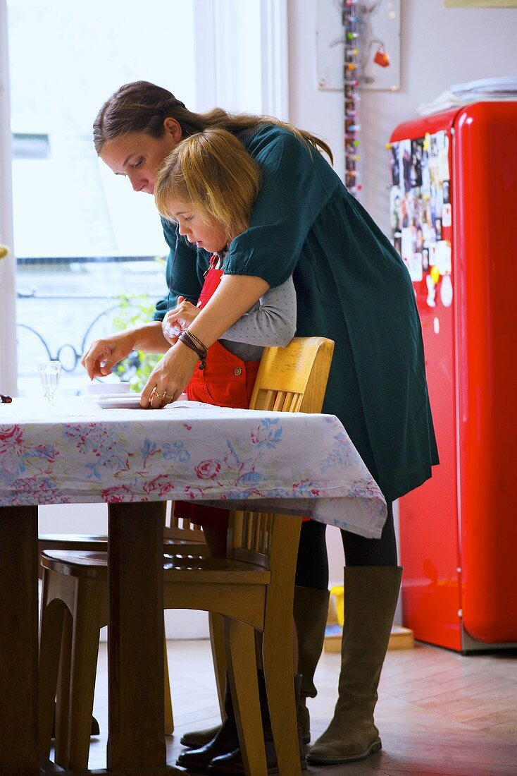 Mother and small daughter laying dining table in kitchen