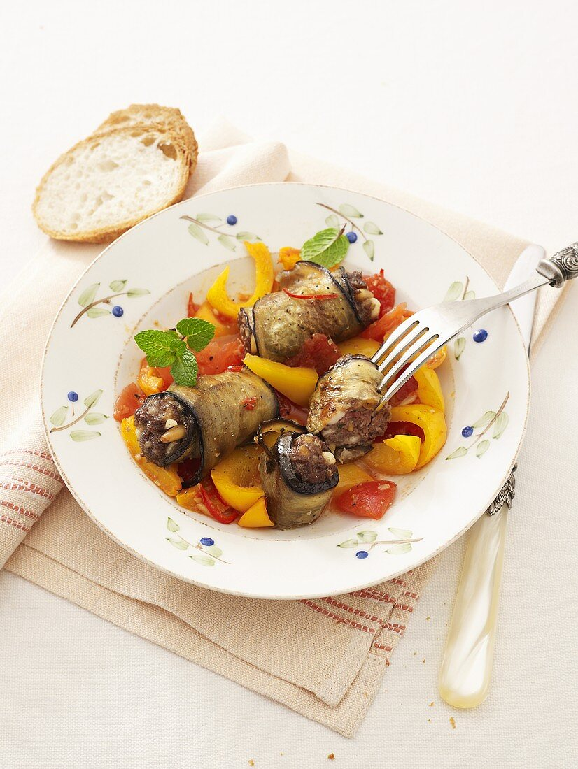Aubergine rolls with mince filling, tomato and pepper ragout