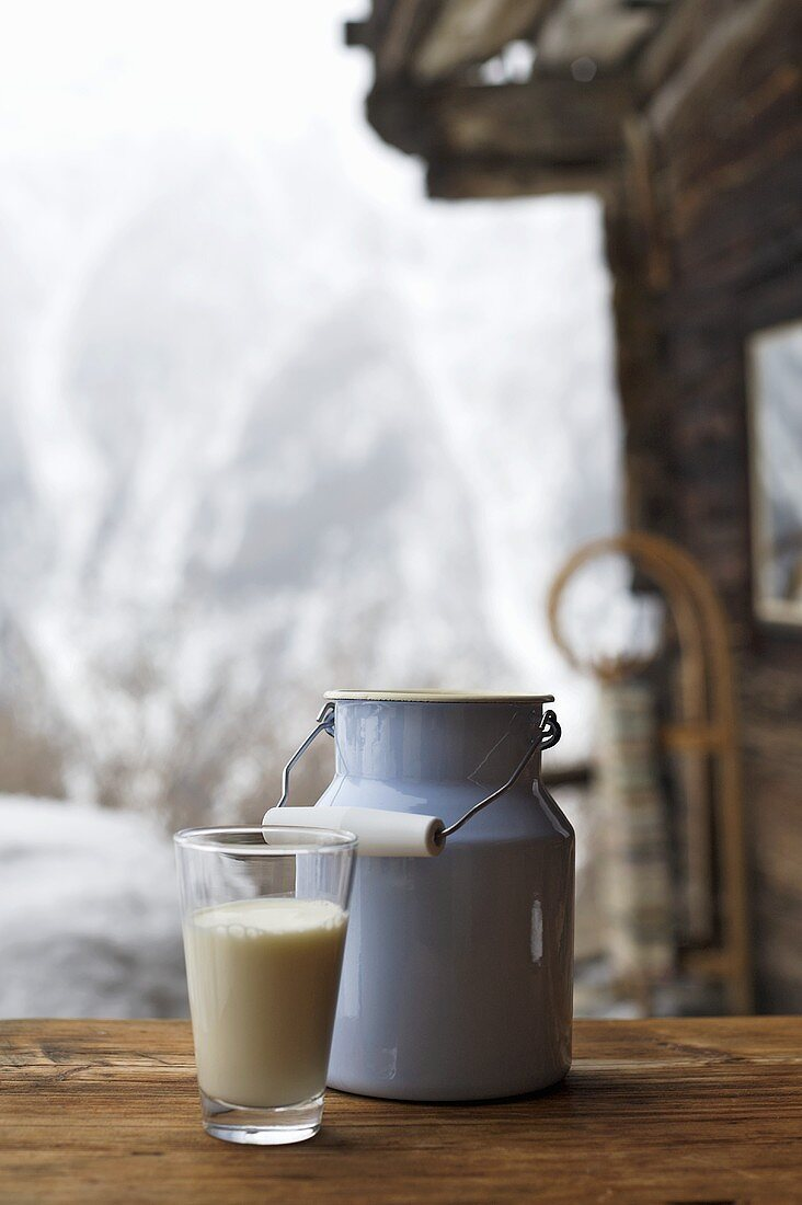 Milk can and glass of milk on table outside Alpine chalet