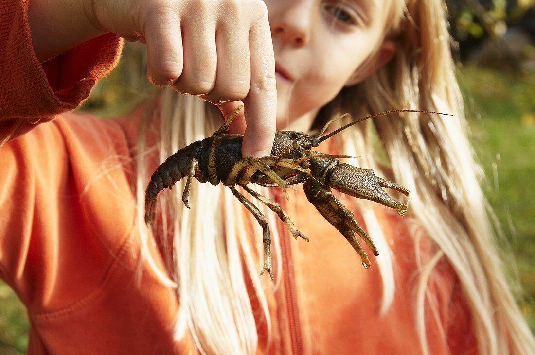 Blond girl holding freshwater crayfish