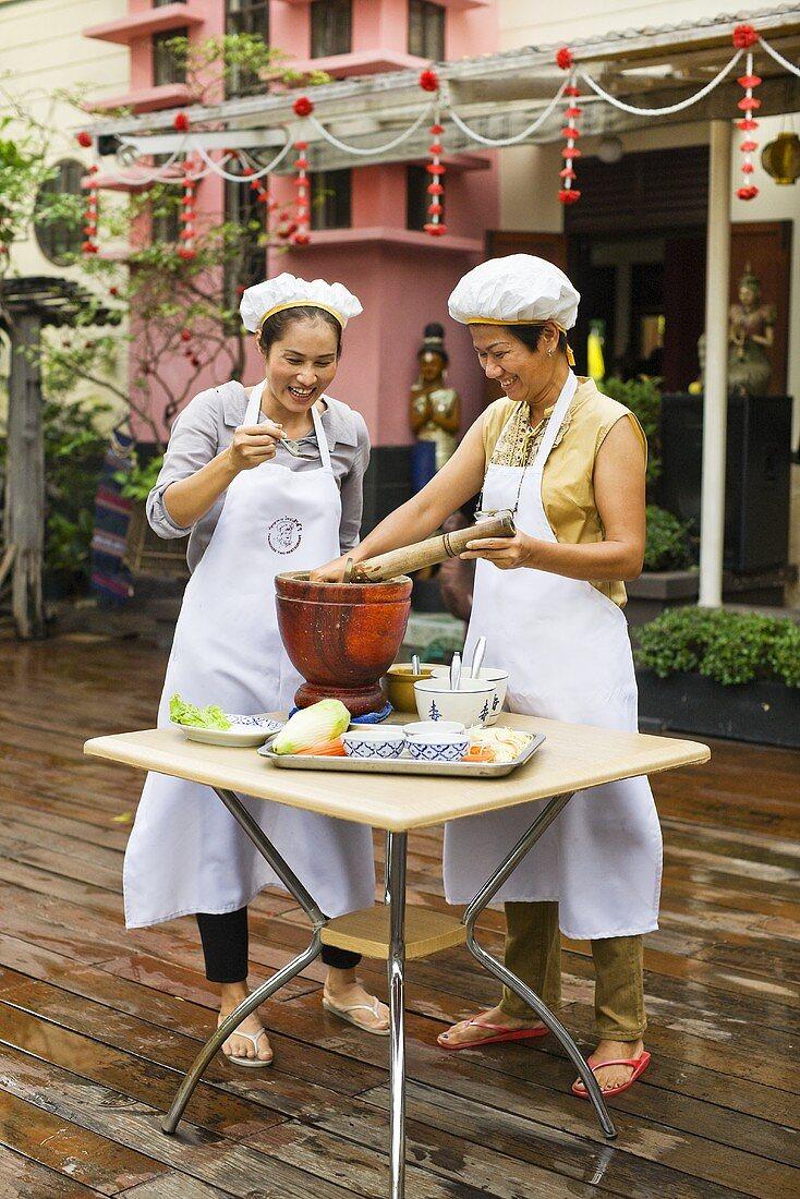 Thai women cooking on terrace