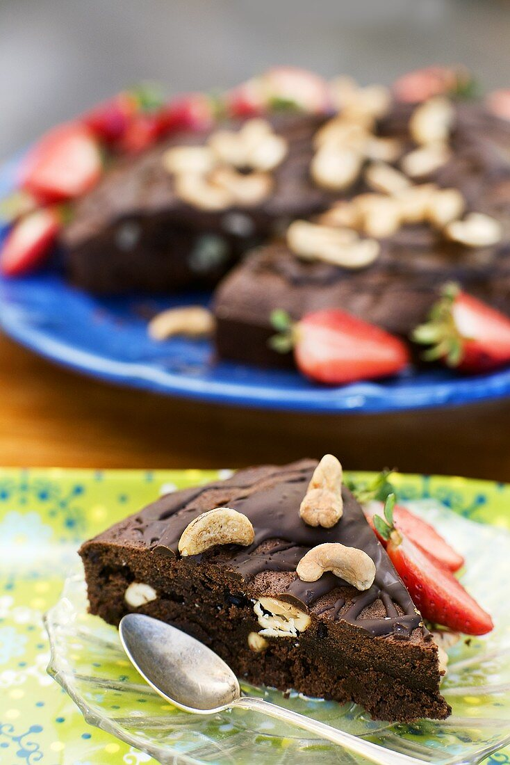 Piece of chocolate cake with cashew nuts and strawberries