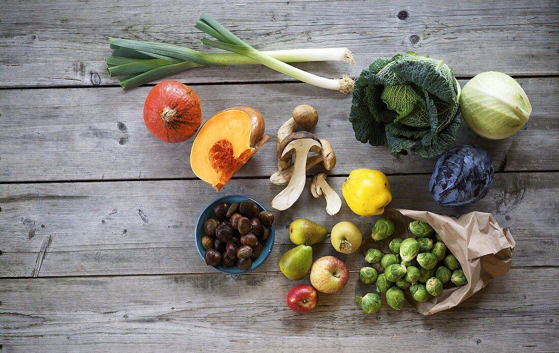 Autumn vegetables, fruit, mushrooms and chestnuts on wood