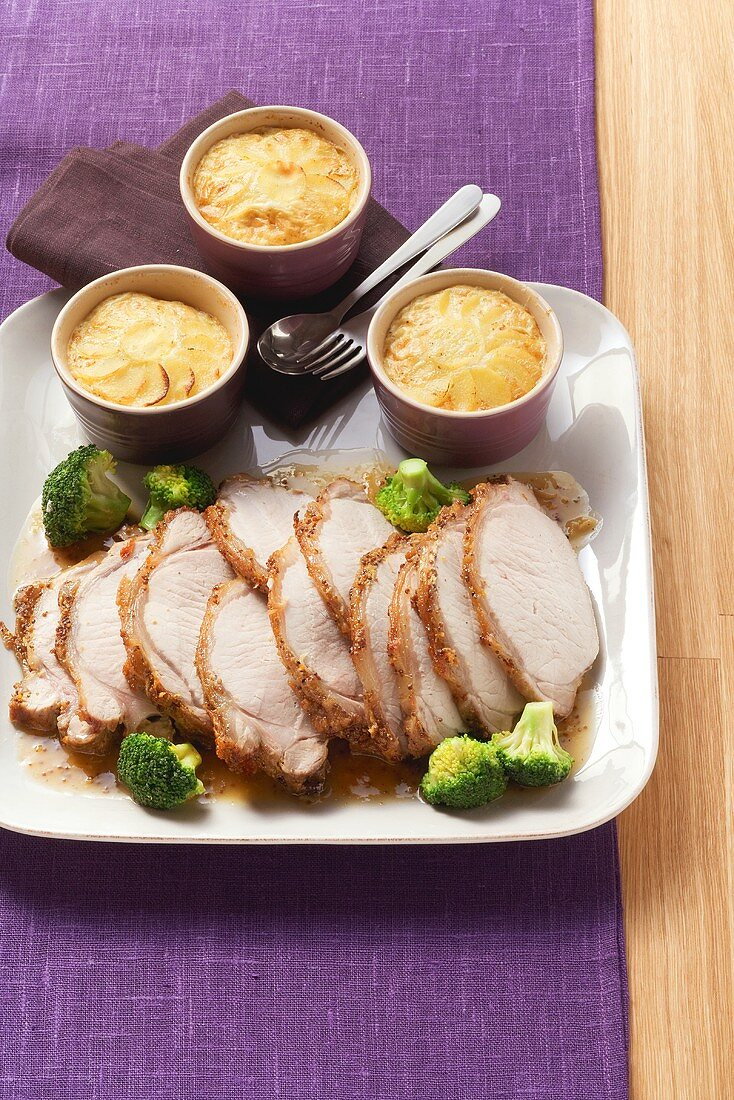 Loin of pork with orange and mustard sauce and potato gratin