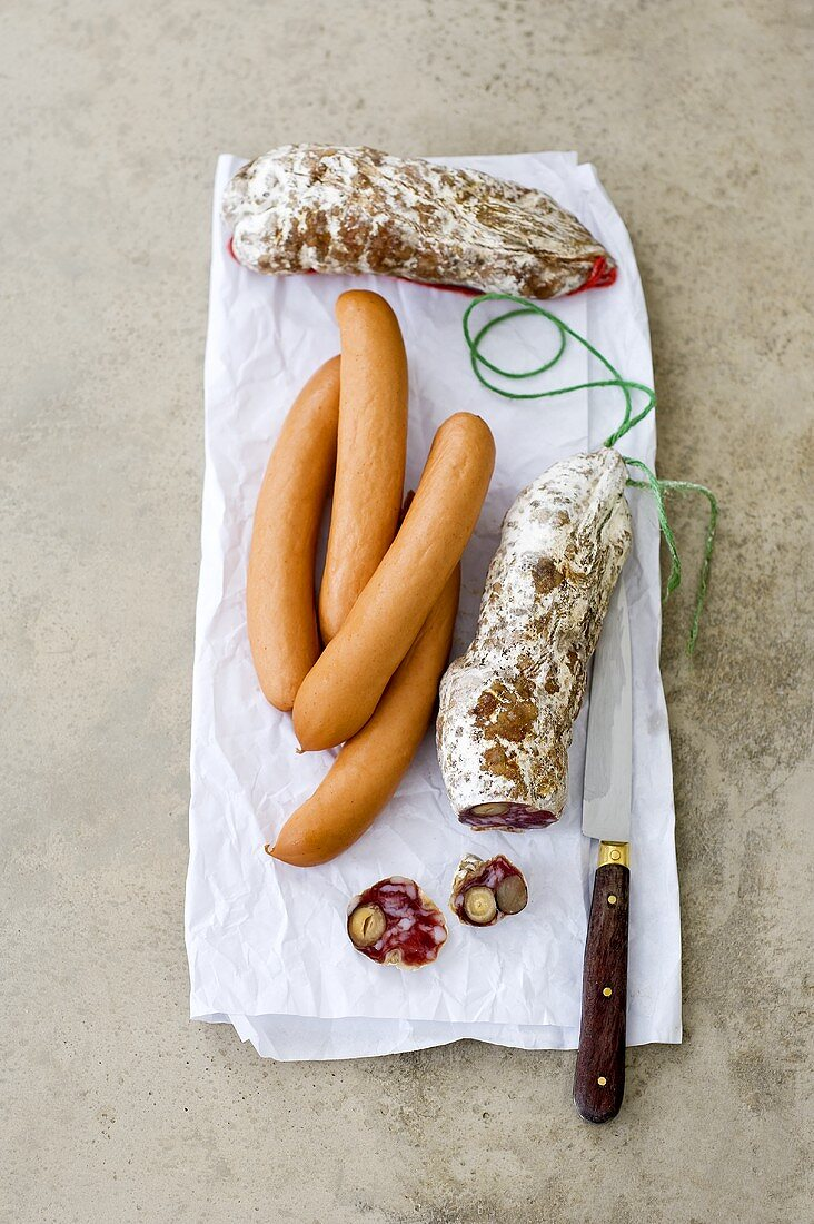 Hard-cured sausages and frankfurters on paper