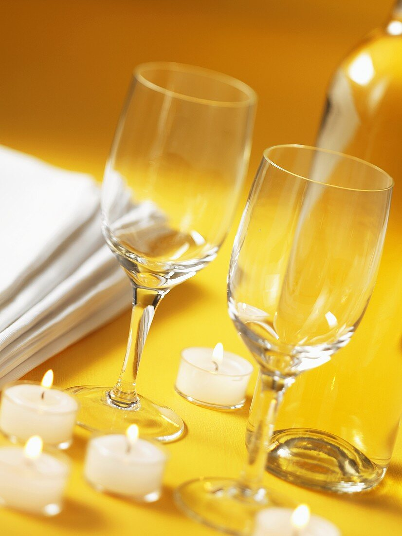 Wine glasses and tealights on yellow background