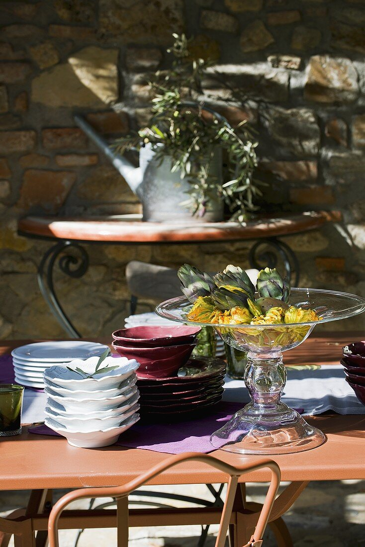 Laid table in front of stone wall (Italy)