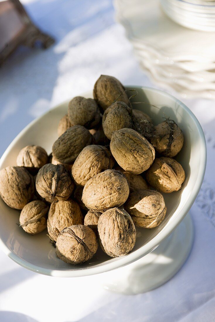 Dish of walnuts on laid table