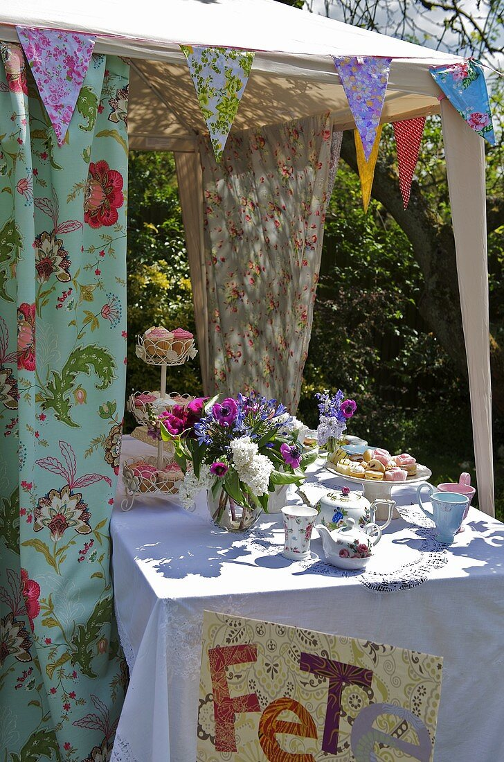 Cakes and tea things on table in pavilion