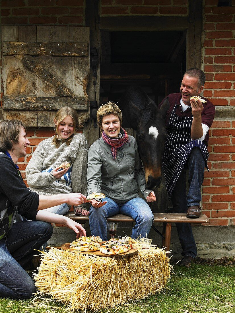 People eating focaccia outside stable