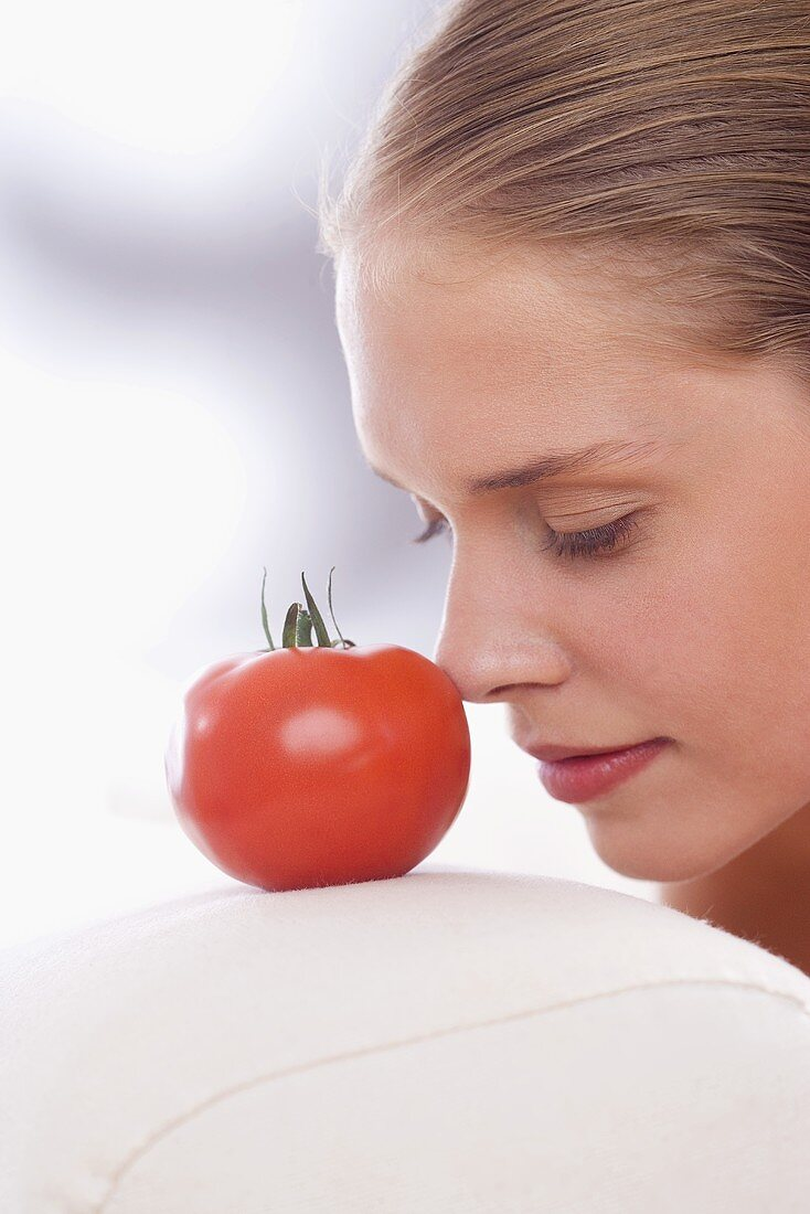 Young woman with the tip of her nose against a tomato