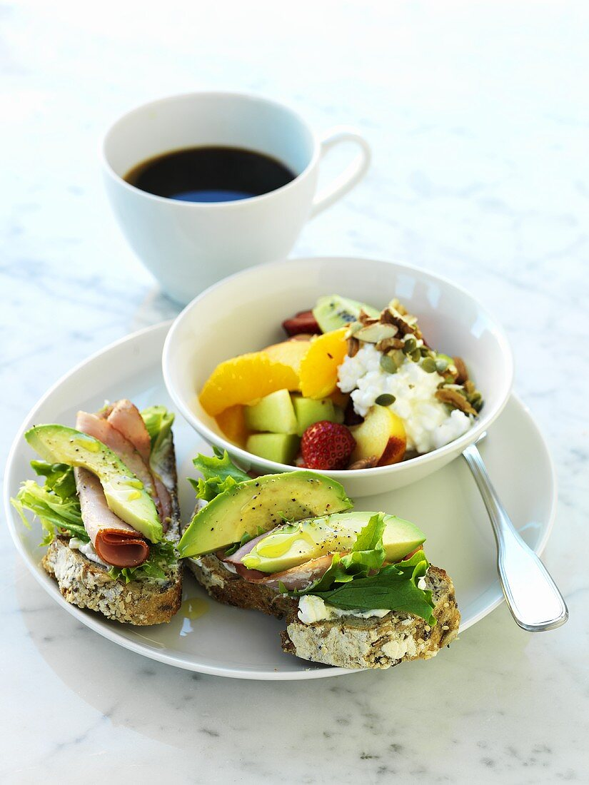 Open sandwiches with avocado, fruit salad with soft cheese, cup of coffee