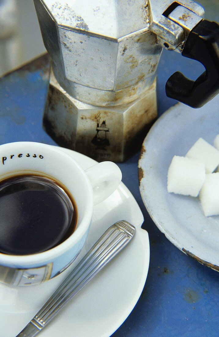 A cup of espresso, sugar cubes and espresso pot