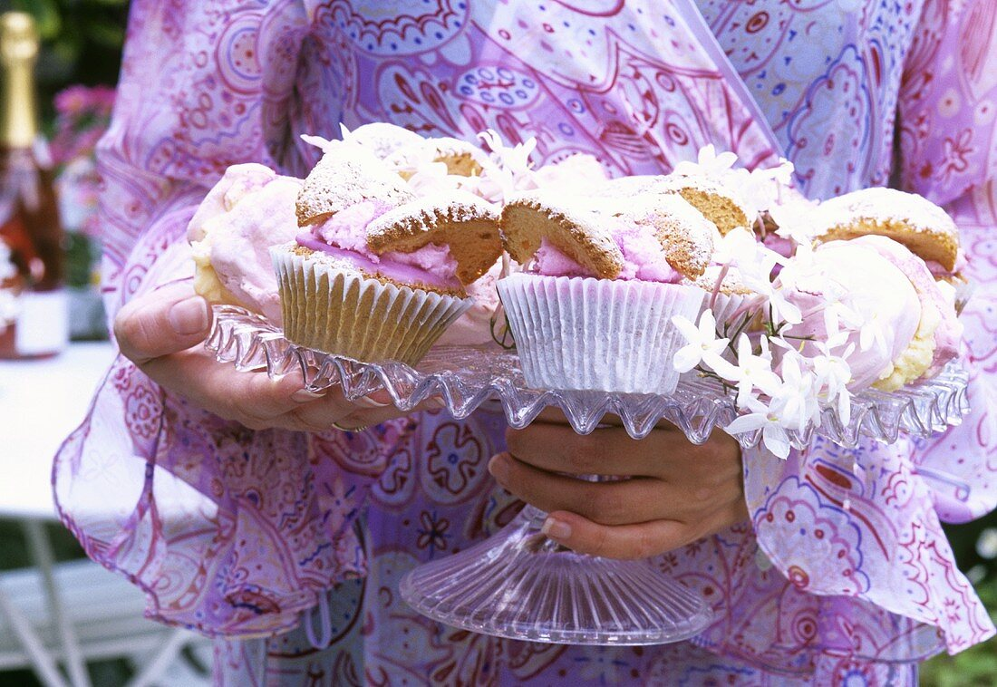 Woman carrying cake stand with cup-cakes and meringues