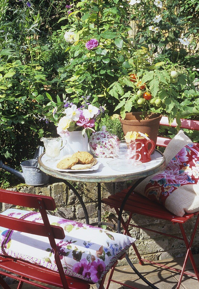 Garden table with tea things, biscuits, flowers and plants