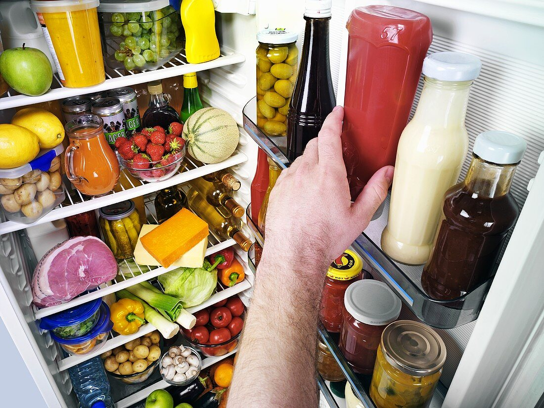 Hand reaching for ketchup bottle in a refrigerator