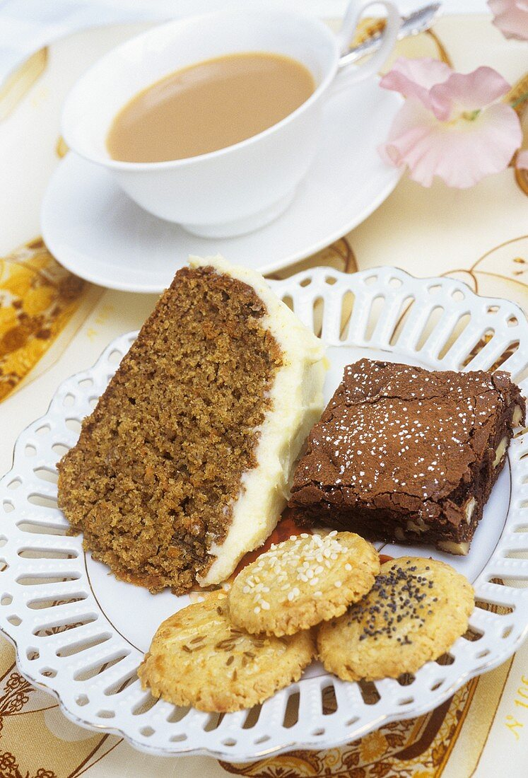 Plate of cakes & biscuits in front of cup of tea with milk