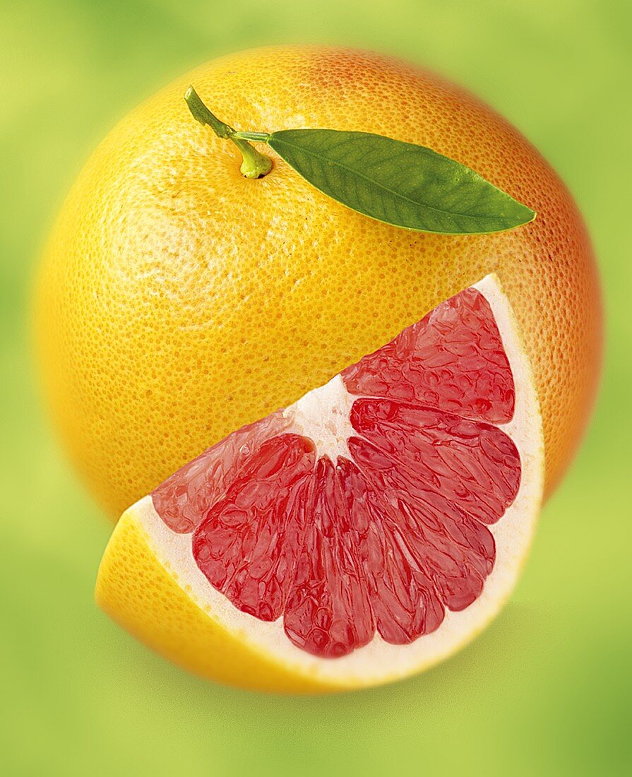 Grapefruit and wedge of grapefruit with pink flesh