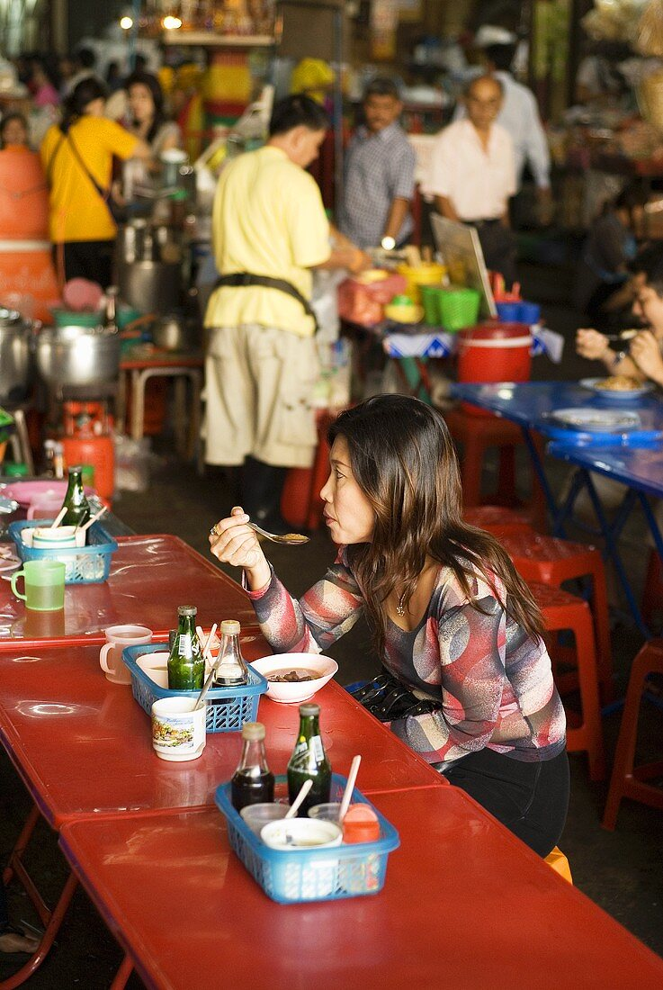 Woman eating at a market in Thailand