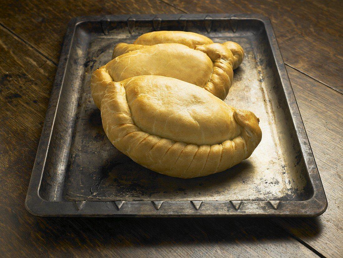 Three Cornish pasties on a baking tray
