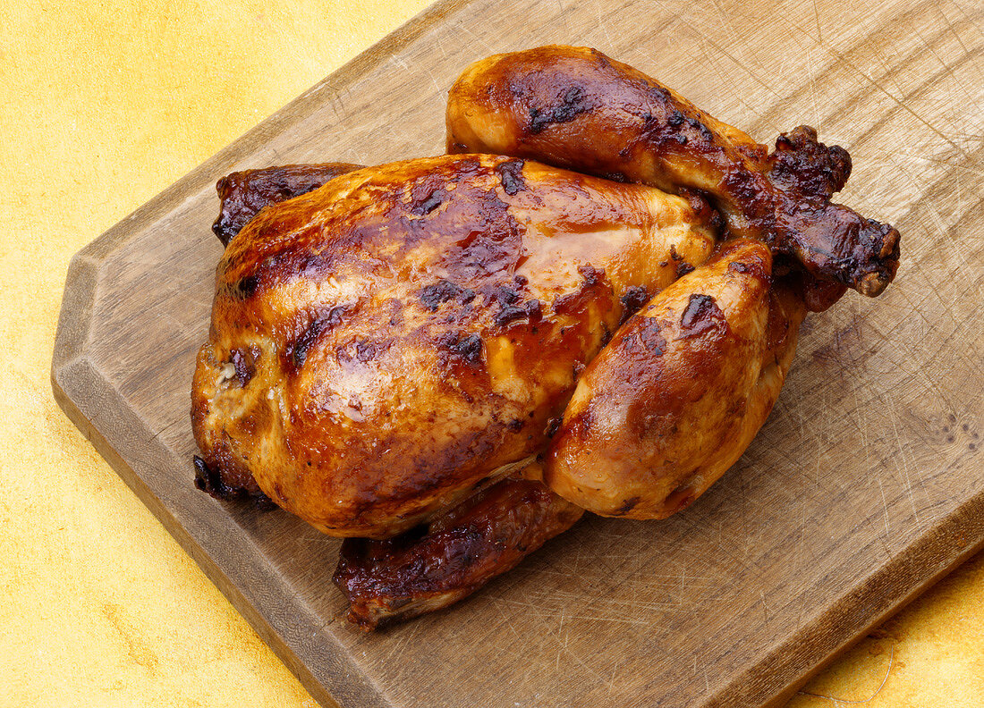 A whole grilled chicken on a wooden board