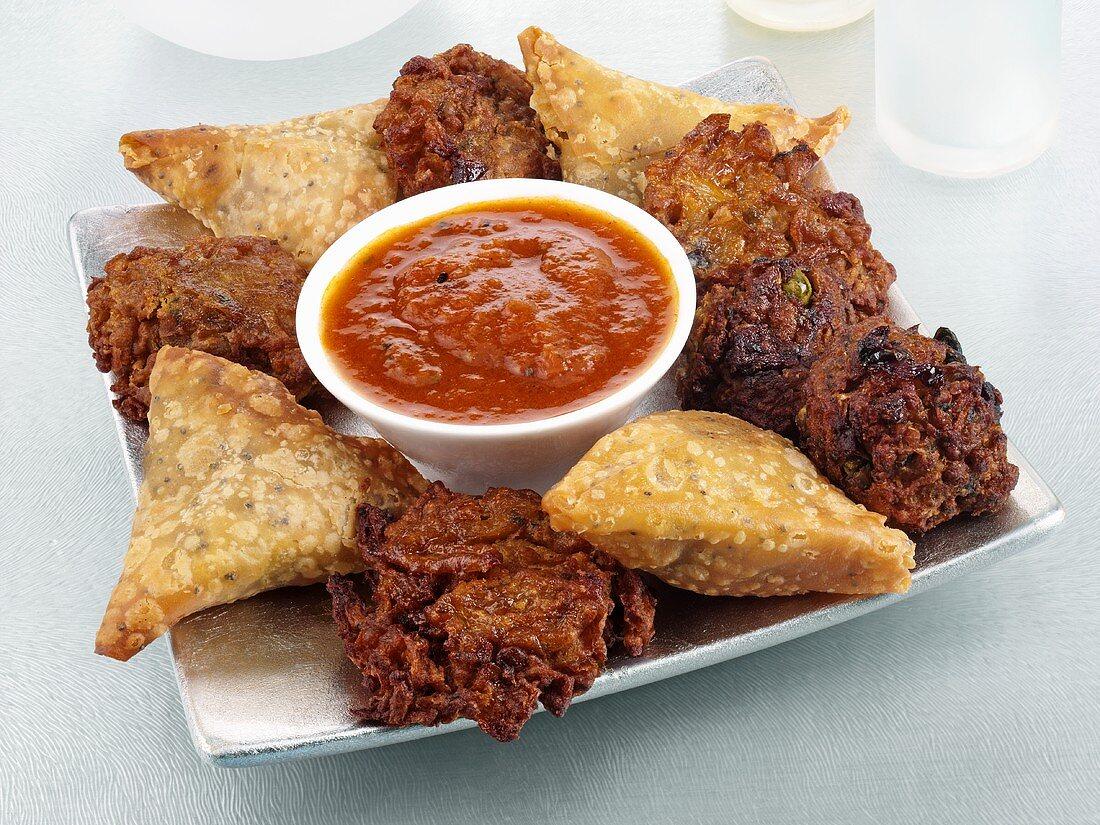 Samosas and bhajis with chilli dip (Indian snacks)