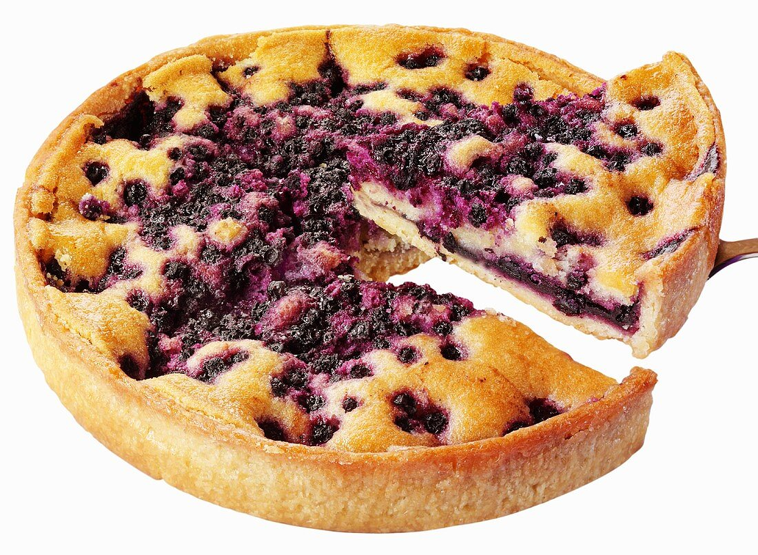 A blueberry tart, a piece cut, with cake slice