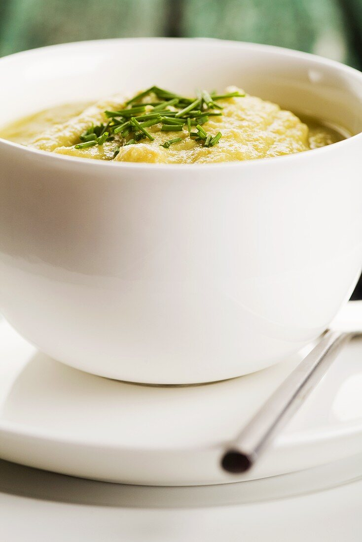 Pea soup with chives in a bowl