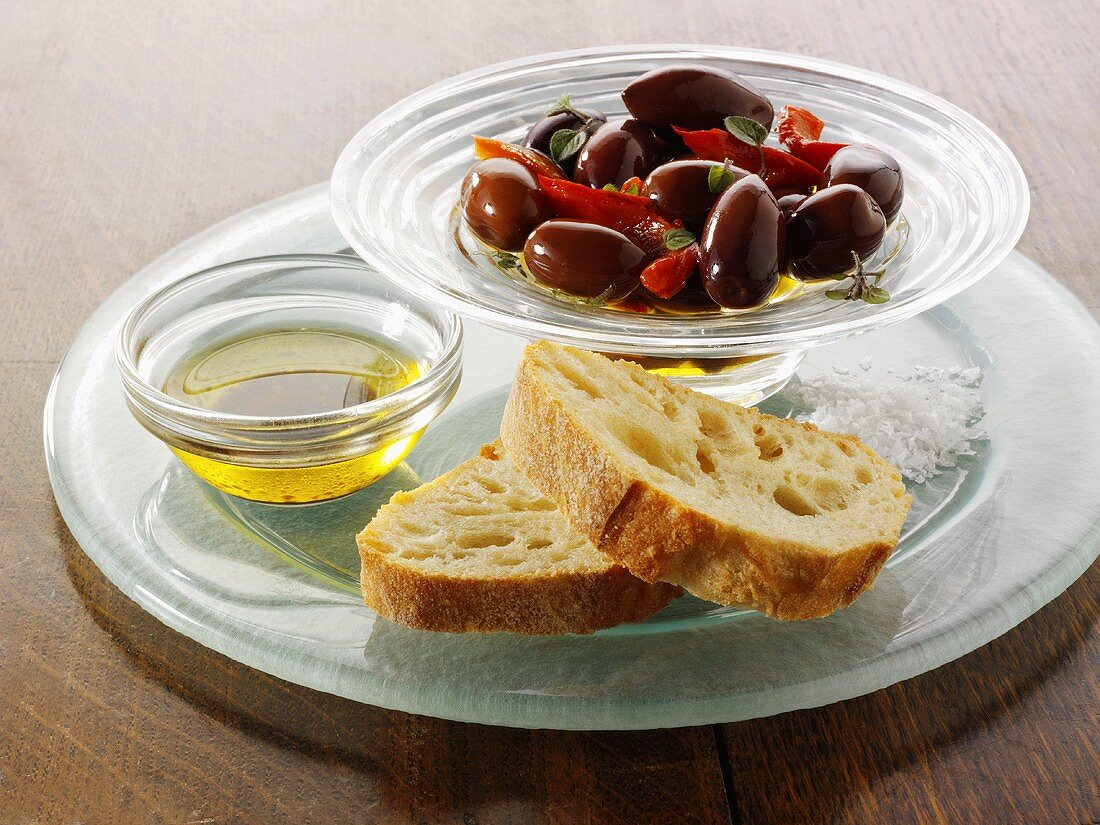 Olives in oil in a small glass dish with white bread