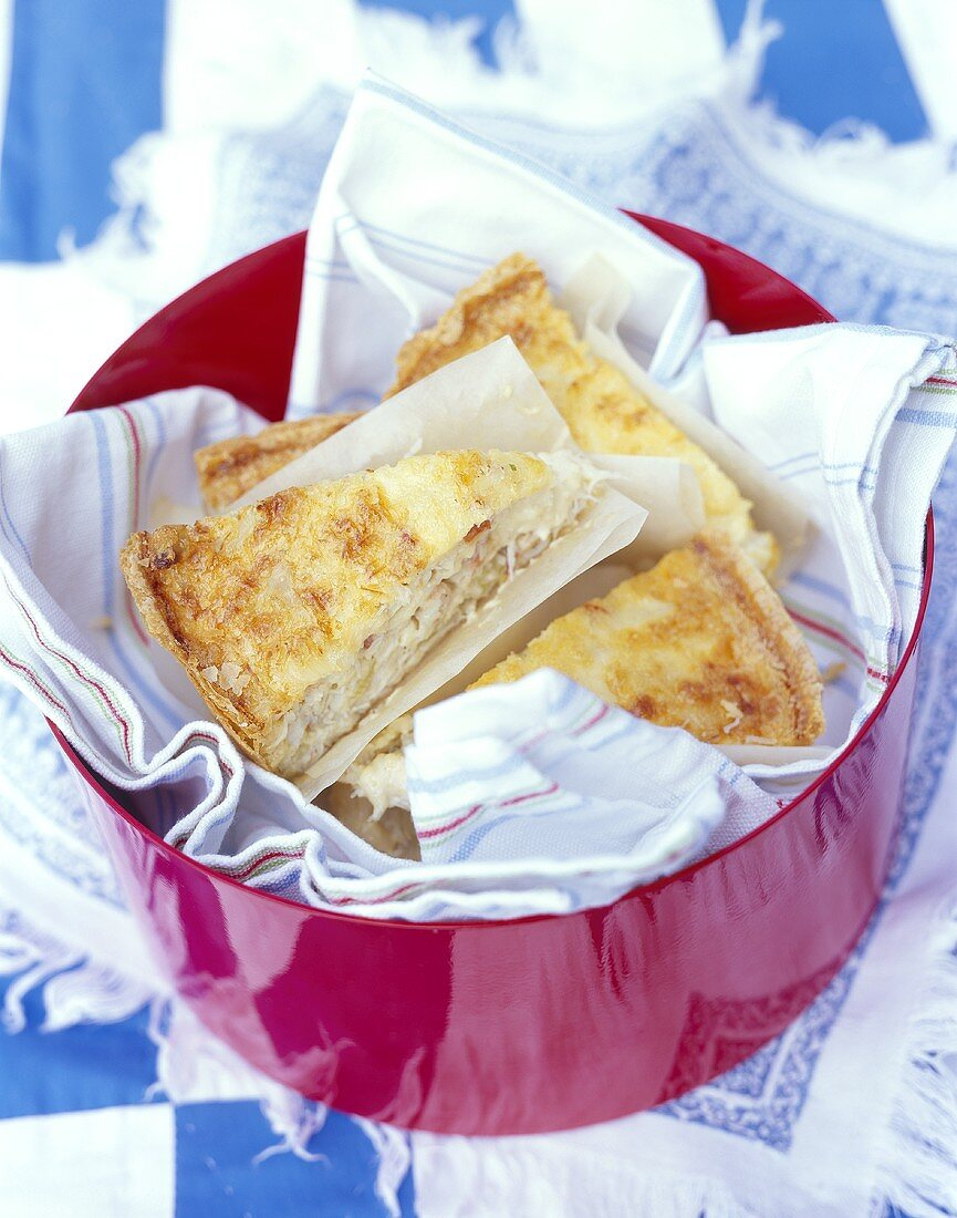 Pieces of shrimp quiche in a bowl with tea towel