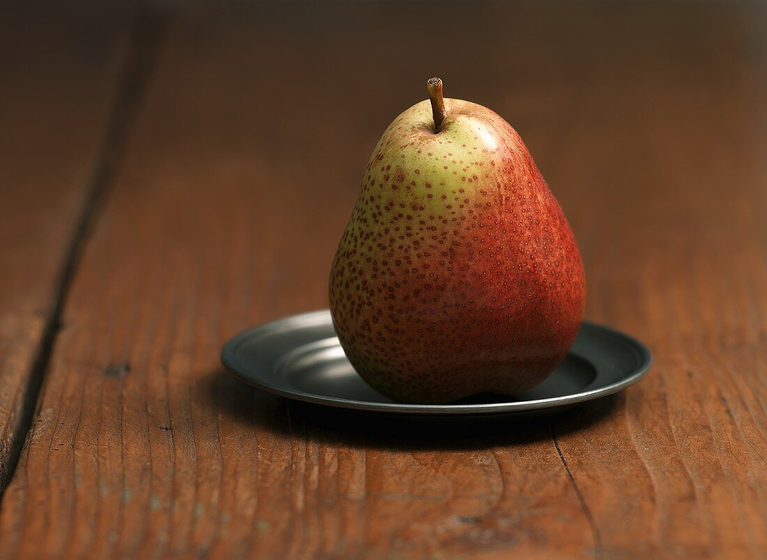 A Forelle pear on a pewter plate