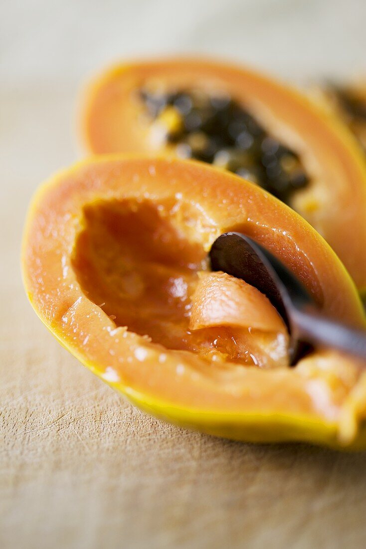 Hollowing out a papaya with a spoon
