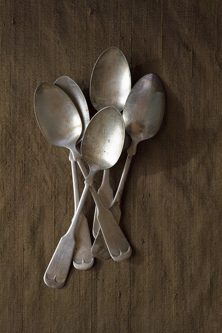 Five antique silver teaspoons (overhead view)