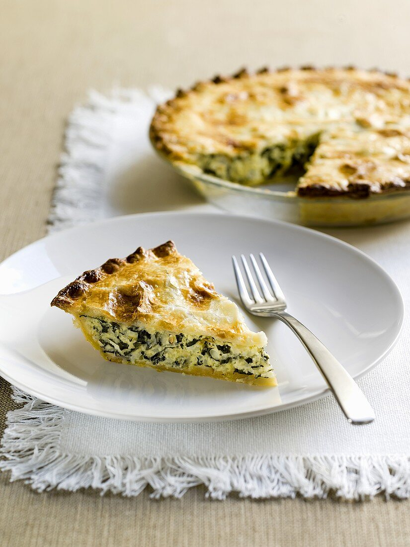 Spinach and rice pie with piece on plate