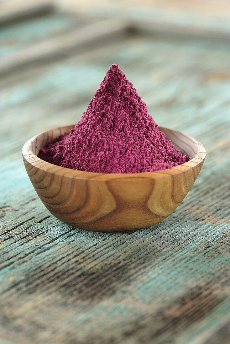 Acai powder (diet aid) in small wooden bowl
