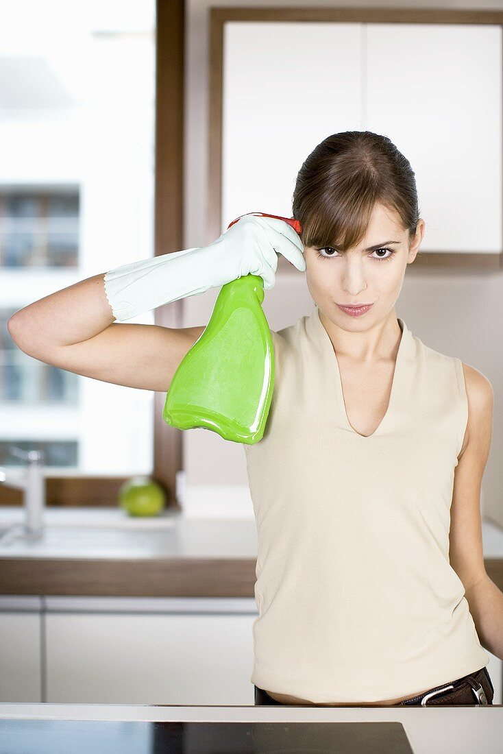 Young woman holding a bottle of cleaning spray to her head