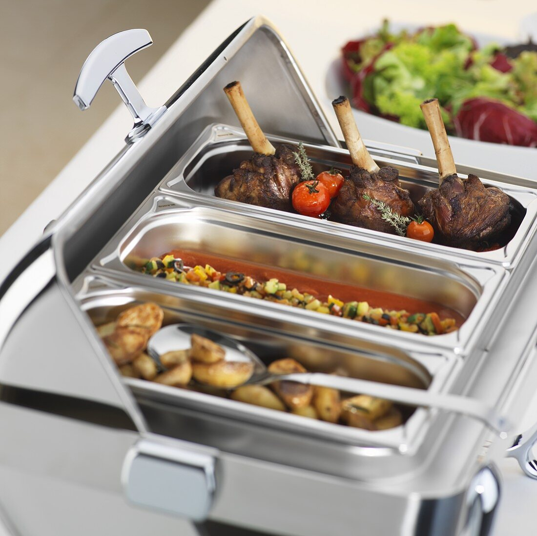 Legs of lamb and vegetables in heated serving counter