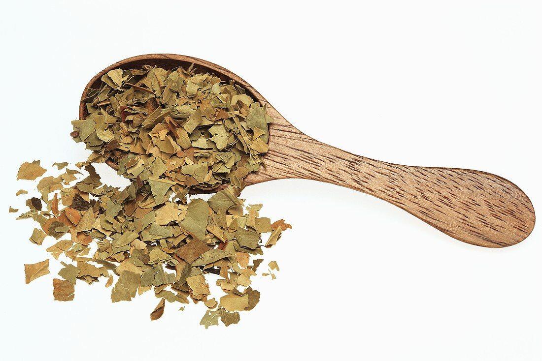 Dried bitter orange leaves on wooden spoon