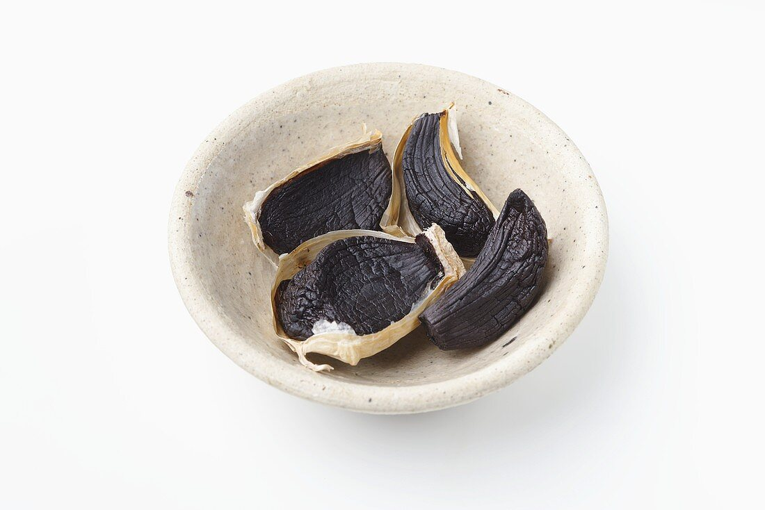 Cloves of black garlic in small dish