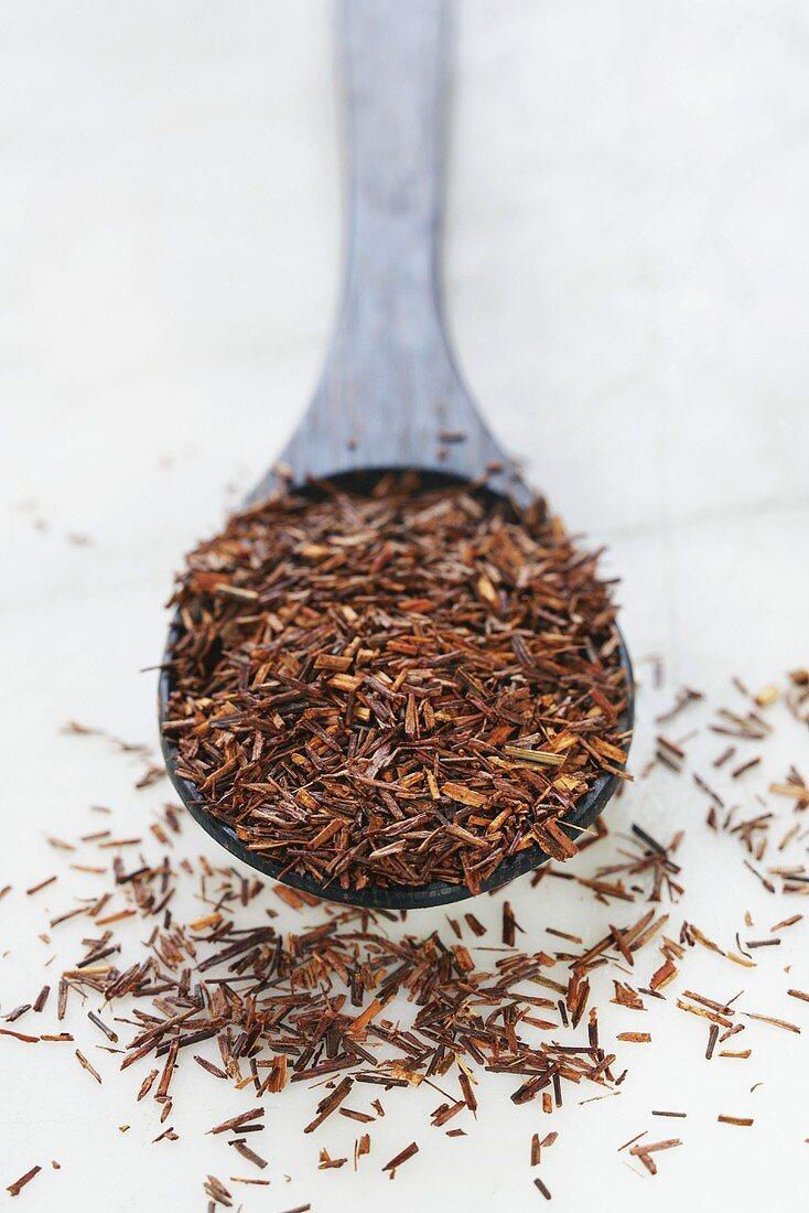 Rooibos tea leaves on wooden spoon