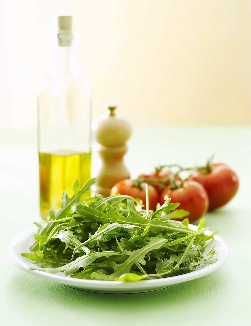Fresh rocket on plate, olive oil, pepper mill, tomatoes