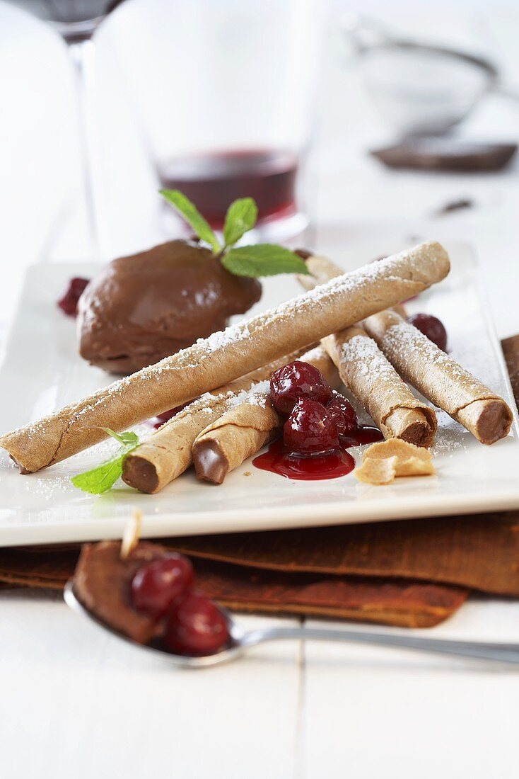 Wafer rolls with chocolate mousse and cherry sauce