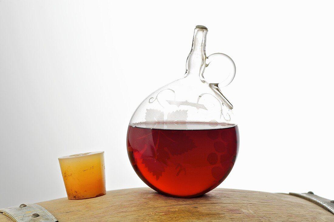 Red wine in glass wine dispenser (Weinheber) on a barrel